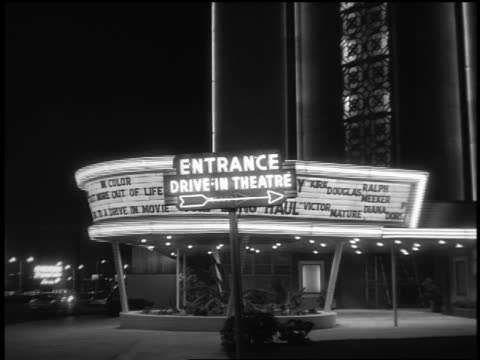 b/w 1940s/50s marquee + neon entrance sign at entrance of drive-in theater at night - theater marquee commercial sign stock videos & royalty-free footage