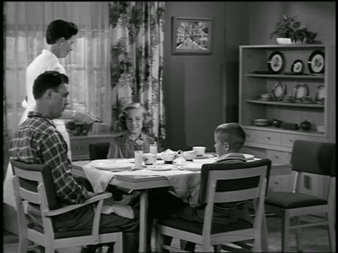 b/w 1940s/50s mother serving juice to man + 2 children at table in dining room / they say grace - 1950 stock videos & royalty-free footage