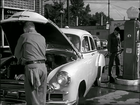b/w 1940s/50s one gas station attendant checks under hood + cleans window while other pumps gas - gas station attendant stock videos and b-roll footage