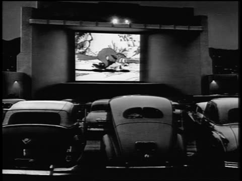 vídeos de stock e filmes b-roll de b/w 1940s/50s rear view cars facing screen playing cartoon at drive in theater at night - 1950