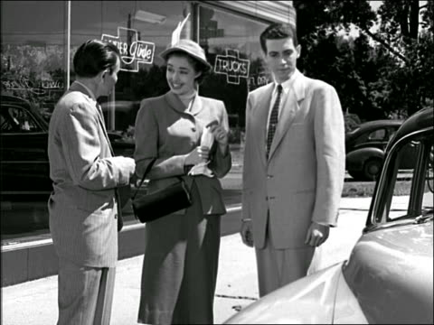 b/w 1940s/50s salesman talks to couple at car dealership / he opens car door for them, they get in - femmina con gruppo di maschi video stock e b–roll