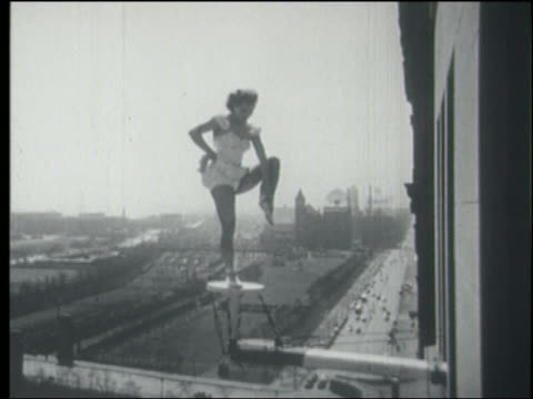 b/w 1940s/50s woman in spangled outfit lifting leg on pedestal over city street - stunt person stock videos & royalty-free footage