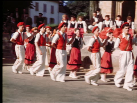 1940s/50s pan young couples in traditional red costumes dancing in village square / france - basco video stock e b–roll
