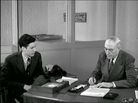 b/w 1940s/50s young man in suit sitting at desk being interviewed by senior businessman - インタビュー点の映像素材/bロール