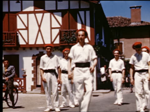1940s/50s young men in red berets + white costumes doing kick-dance in village street / France