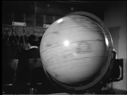 B/W 1940s/50s zoom out dolly shot from spinning globe to woman with phone book looking at globe / operators in background
