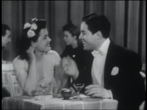 b/w 1941couple in formalwear sitting at table in nightclub / man kisses woman's hand - kissing hand stock videos & royalty-free footage