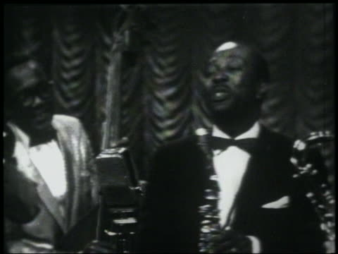 stockvideo's en b-roll-footage met b/w 1950/60s louis jordan singing choochoo chboogie at mike on stage while holding saxophone - saxofonist
