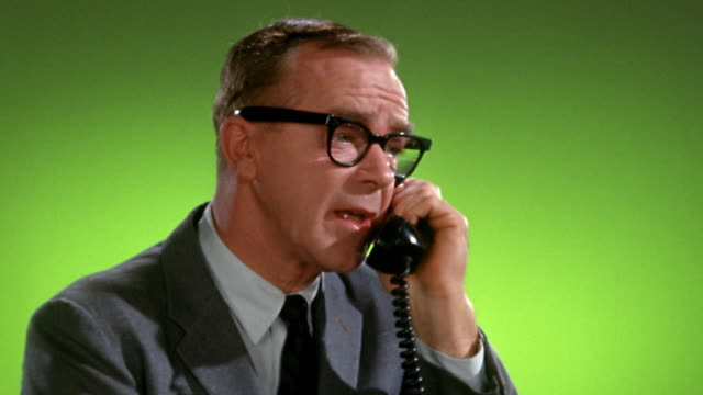 1950s / 1960s medium shot man in suit and dark-framed eyeglasses talking on telephone / green background
