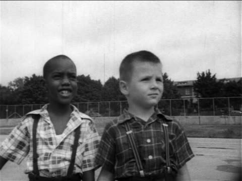 b/w 1950s 2 boys, 1 black, 1 caucasian, standing on playground looking at something off screen - caucasian appearance stock videos & royalty-free footage