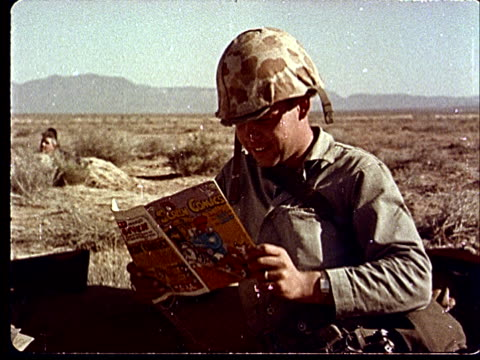 1950s ms army soldier in camouflage helmet reading comic book at camp desert rock at nevada test site / nye county nevada usa - army helmet stock videos & royalty-free footage