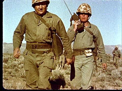 vídeos y material grabado en eventos de stock de 1950s ws army soldiers marching through desert while one man talks on walkietalkie radio at camp desert rock at nevada test site / nye county nevada... - walkie talkie