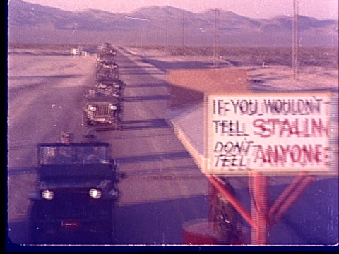 1950s HA WS POV Army vehicles driving toward entrance to Nevada Proving Ground past sign reading 'If You Wouldn't Tell Stalin Don't Tell Anyone' at...
