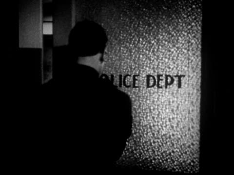 """""""1950s ms back of police officer entering office through swinging door at police department/ redondo beach, california/ audio"""" - polizeirevier stock-videos und b-roll-filmmaterial"""