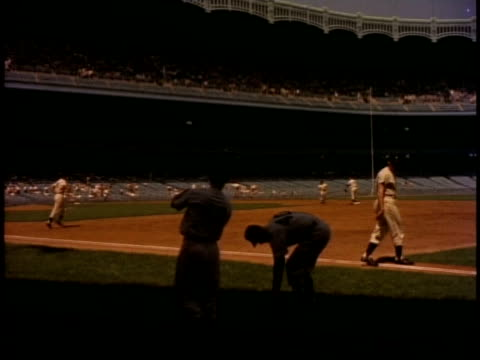 1950s ws pan baseball players warming up on field in yankee stadium / new york, new york, usa - reportage stock videos & royalty-free footage