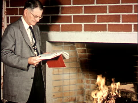 1950s MS, Berkeley University professor reading book beside fireplace, 1950's, California, USA