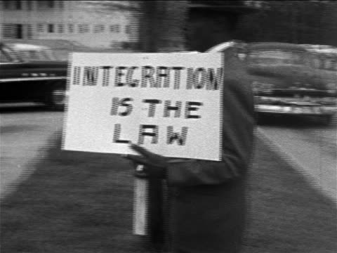 b/w 1950s black male demonstrator carrying sign integration is the law on sidewalk / texas - human rights stock videos & royalty-free footage