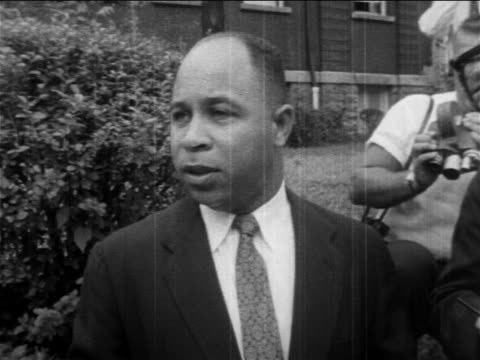 b/w 1950s black male official talking to camera in front of school / prosegregation protests - アメリカ黒人の歴史点の映像素材/bロール