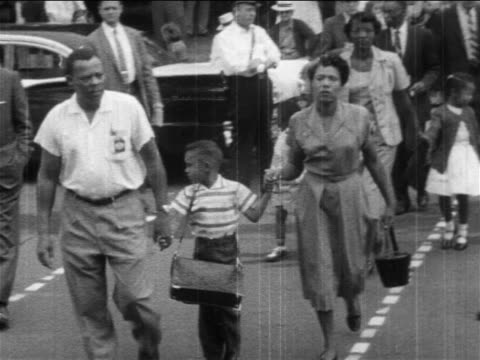 1950s black parents walking their children on street to desegregated school / newsreel - newsreel stock videos & royalty-free footage