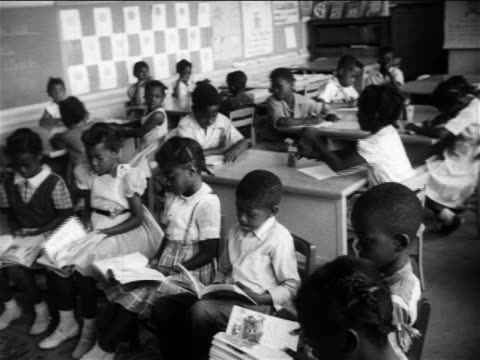 B/W 1950s Black schoolchildren sitting in semicircle + at desks in classroom / newsreel