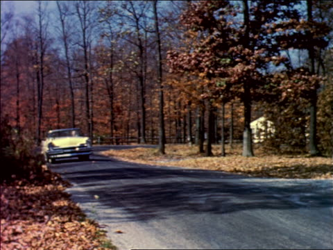 1950s pan blonde woman driving yellow convertible lincoln on country road in autumn / passing house - ford motor company stock videos and b-roll footage
