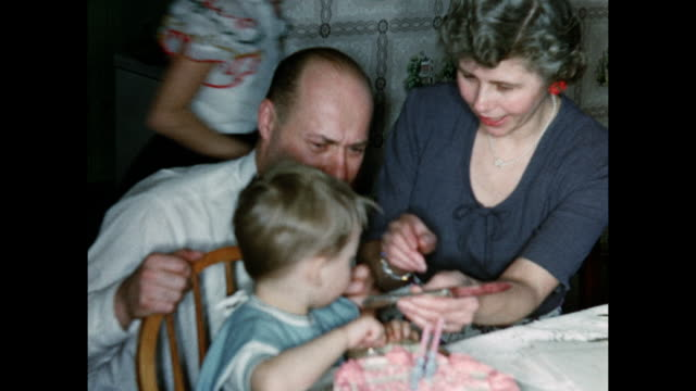 1950s boy cuts cake with parents help home movie - シャツとネクタイ点の映像素材/bロール