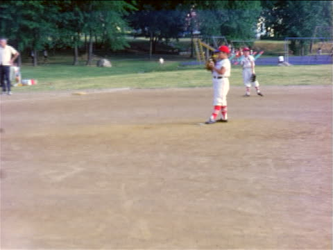 1950s boy in baseball uniform holding ball on pitcher's mound / home movie
