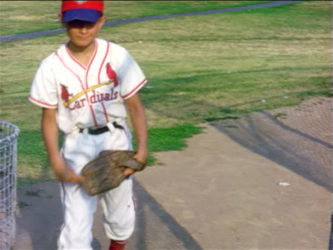 vidéos et rushes de 1950s boy in baseball uniform with baseball glove squatting then walking toward camera / home movie - casquette de baseball