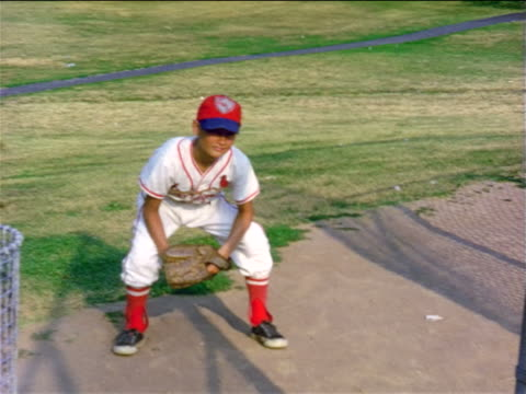 vidéos et rushes de 1950s boy in baseball uniform with mitt squatting on field / home movie - casquette de baseball