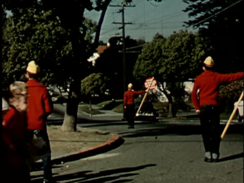 1950s MS, PAN, Boys in junior police uniforms holding stop signs on street, group of children crossing street,1950's, Berkeley, California, USA