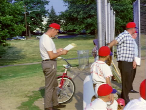 vidéos et rushes de 1950s boys + men in red baseball caps standing by fence at little league game / home movie - casquette de baseball