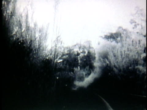 1950s b/w montage viet cong soldiers running down railroad as sabotaged bridge explodes / vietnam - ベトコン点の映像素材/bロール