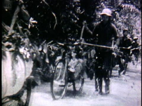 1950s b/w ms vietnamese peasants transferring supplies by bicycles through jungle / north vietnam - north vietnam stock videos & royalty-free footage