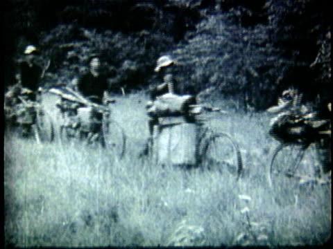 1950s b/w ws vietnamese peasants transferring supplies by bicycles through jungle / north vietnam - north vietnam stock videos & royalty-free footage