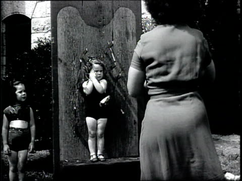 1950s B/W Woman throwing knives at small child standing against a board