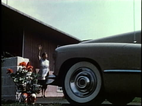 1950s la car backing from driveway, woman waving and picking up newspaper / levittown, pennsylvania, united states - levittown pennsylvania stock videos and b-roll footage