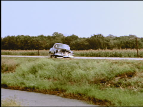 1950s pan car driving off side of road into ditch full of water + mud - 横滑り点の映像素材/bロール