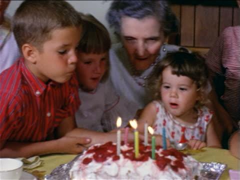1950s children helping senior woman blow out candles on birthday cake / home movie - kindergeburtstag stock-videos und b-roll-filmmaterial