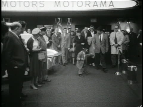 B/W 1950s chimpanzee in suit walking with crowd of people / newsreel