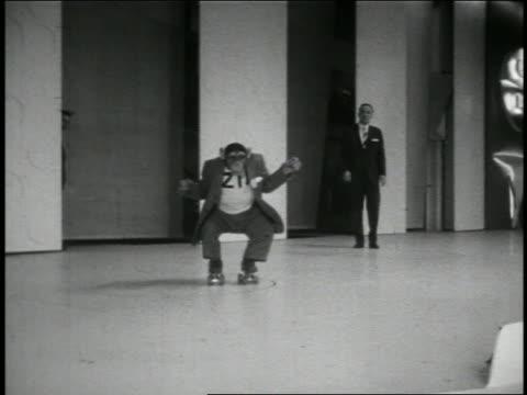 "stockvideo's en b-roll-footage met b/w 1950s chimpanzee ""zip"" in suit coming towards camera on roller skates / newsreel - compleet pak"