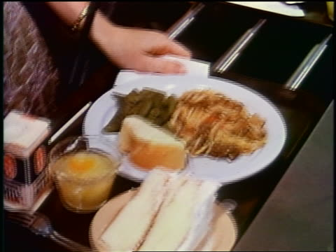 1950s close up children's hands pushing trays of food in school cafeteria / newsreel - cafeteria bildbanksvideor och videomaterial från bakom kulisserna