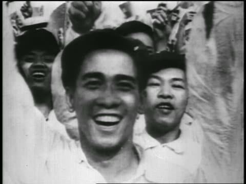 vídeos y material grabado en eventos de stock de b/w 1950s close up excited young asian man waving in crowd / north vietnam / newsreel - toothy smile