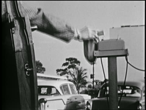 b/w 1950s close up hand of man reaching out of car + grabbing speaker at drive in movie - bühnentheater stock-videos und b-roll-filmmaterial