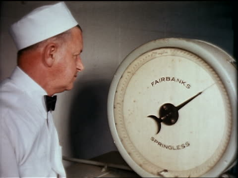 "1950s close up man in uniform watching needle moving on ""fairbanks"" scale in ice cream factory - waage gewichtsmessinstrument stock-videos und b-roll-filmmaterial"