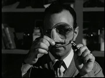 vídeos y material grabado en eventos de stock de 1950s close up man looking at bullet through magnifying glass / tilt down to tagged gun - detective
