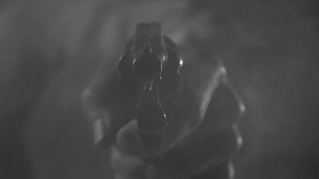 1950s close up man' s hand firing gun / gun smoking - arma da fuoco video stock e b–roll