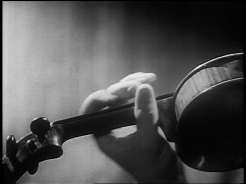B/W 1950s close up man's fingers playing violin