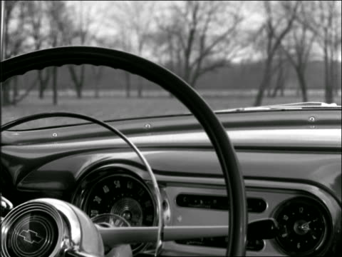 b/w 1950s close up man's hand puts car into gear / point of view thru steering wheel of countryside - steering wheel stock videos & royalty-free footage