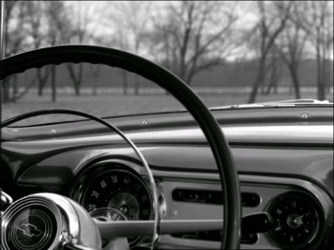 vidéos et rushes de b/w 1950s close up man's hand puts car into gear / point of view thru steering wheel of countryside - intérieur de véhicule