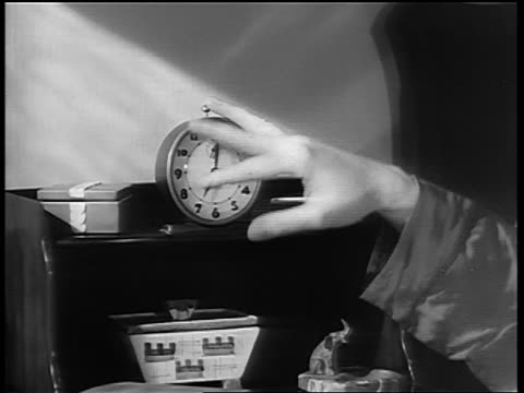 b/w 1950s(?) close up man's hand turning off ringing alarm clock on night table - yorkville illinois stock videos & royalty-free footage
